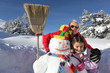 Little girl and granddad with their snowman