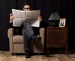 Man with newspaper sitting in vintage armchair