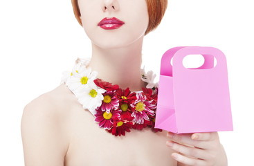 Beautiful redhead girl with flowers and gift box