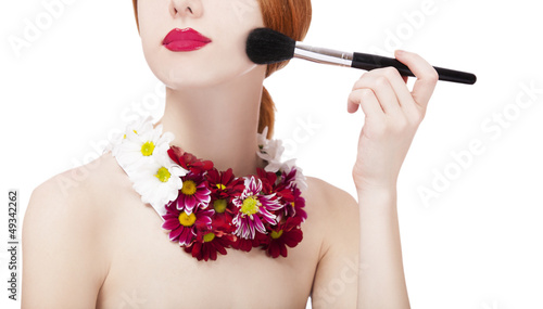 Beautiful redhead girl with flowers and makeup brush