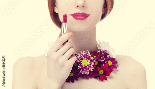Beautiful redhead girl with flowers holding lipstick