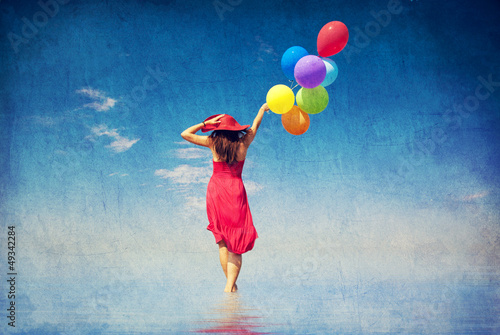 Brunette girl with colour balloons at coast.