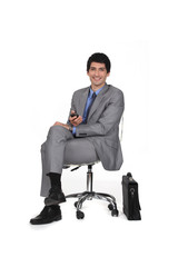 Businessman sitting on a chair and watching TV