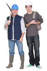 Tradesman standing next to  apprentice