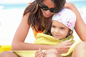Mother drying daughter with towel at the beach