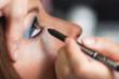 Visagistin trägt Eyeliner auf