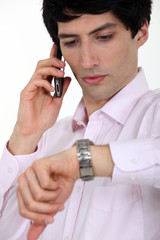 A businessman over the phone looking at his watch.