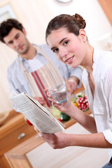 Couple in the kitchen with a newspaper