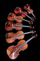 different sized violins on black