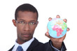 Concept shot of a businessman holding a miniature globe