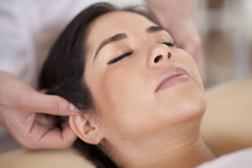 Beautiful chubby woman getting an ear massage at a spa