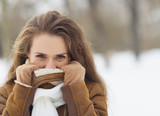 Young woman hiding in winter jacket outdoors
