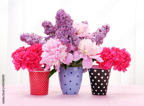 spring flowers in cups on table on white wooden background