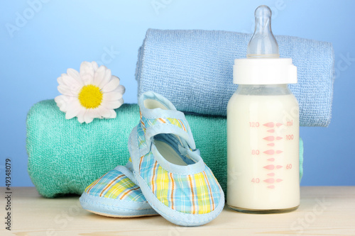 Baby bottle of milk with baby's bootees near towels