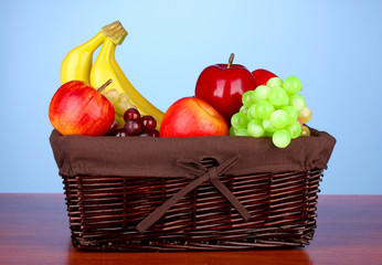 Wicker basket with fruits on color background