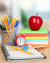 School supplies with apple and clock on wooden table