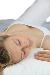 Woman in white asleep on a white bed
