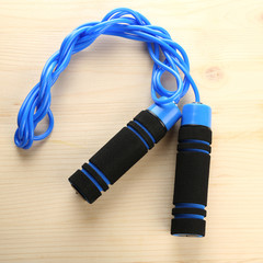 Blue skipping rope, on wooden background