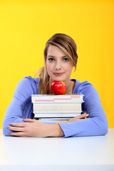 Student with books and red apple