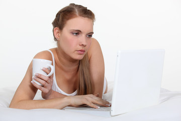Young woman laying on bed with laptop and coffee