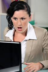 Shocked woman reading an e-mail