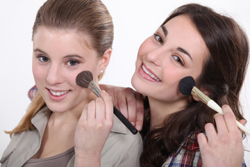 Young women putting on makeup