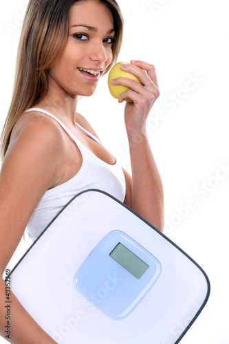 woman holding apple and bathroom scales