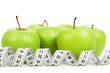 Measuring tape around a green apples as a symbol of diet.