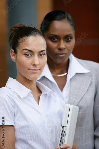 Two businesswomen stood with laptop
