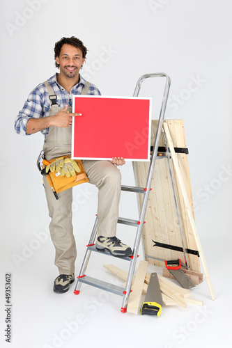 Male builder holding message board