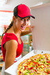 Woman holding a whole pizza in hand