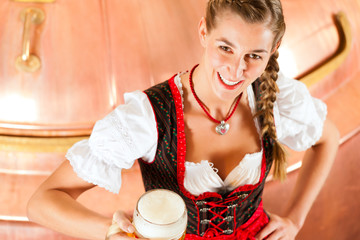 Woman with beer glass in brewery