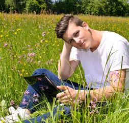 Junger Mann arbeitet mit Notebook auf Wiese