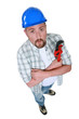 Grumpy plumber posing with wrench