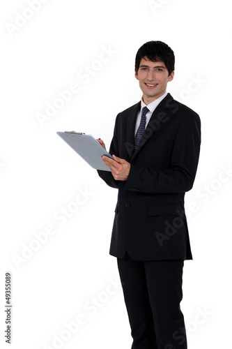 Businessman writing on his clipboard