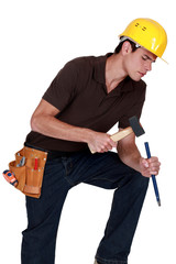Carpenter concentrating with a hammer and chisel