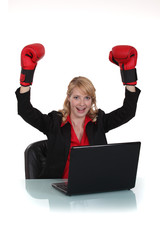 Excited businesswoman wearing boxing gloves at desk