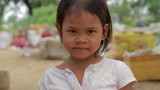 Cambodian girl in slums, garbages at background