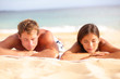 Young couple relaxing sleeping on beach