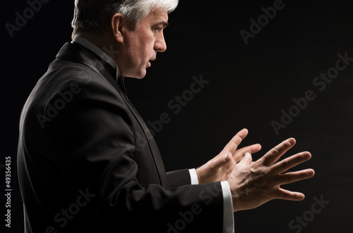 Closeup portrait of male orchestra conductor directing with his