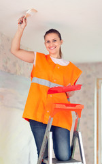 Female house painter paints the ceiling