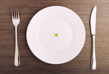 diet concept. one pea on an empty white plate