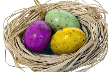 Trio of Easter eggs in a nest isolated on white.