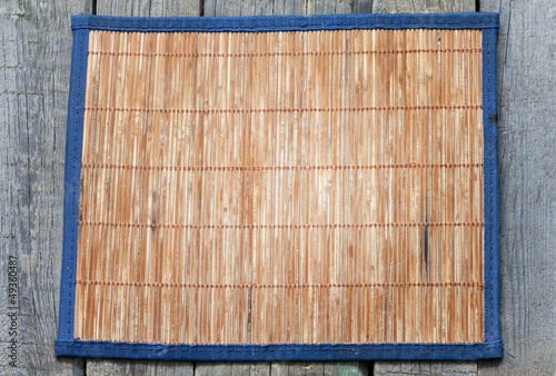 Bamboo mat on vintage wooden boards food background concept