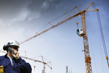 construction worker talking in phone, machinery in background