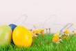 mehrere Metall Osterhasen mit bunten Eiern auf grüner Wiese