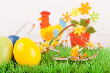 Osterhasen auf grüner Wiese mit bunten Eiern und Deko