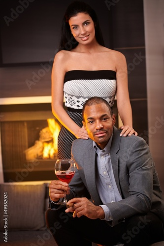 Attractive interracial couple at home by fireplace