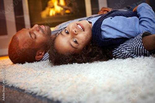 Little girl and father lying on floor at home