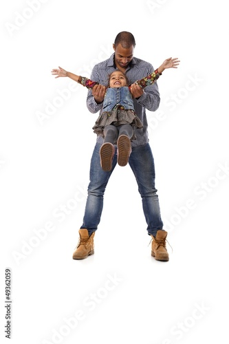 Ethnic man playing with little daughter having fun